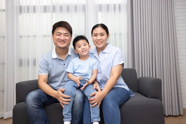 Szczęśliwa azjatycka rodzina z małym synkiem siedzi razem na kanapie w domu