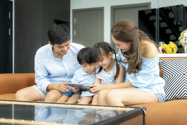 Szczęśliwa azjatycka rodzina z ojcem, matką, córką i synem, siedząc na kanapie i za pomocą cyfrowego tabletu