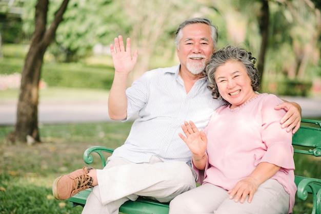Szczęśliwa azjatycka starsza para macha rękę i ono uśmiecha się plenerowych w parku