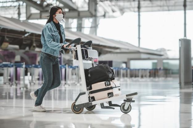 Szczęśliwa azjatycka turystka z maską chroniącą przed koronawirusem chodząca z wózkiem bagażowym