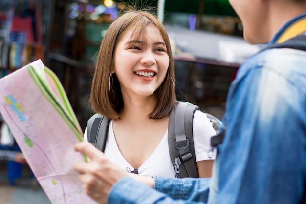 Szczęśliwa azjatycka turystyczna para backpacking w bangkok tajlandia