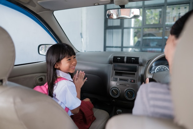 Szczęśliwa azjatycka uczennica szkoły podstawowej, która rano jedzie samochodem z rodzicem do szkoły