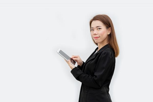Szczęśliwa azjatykcia biznesowa kobieta używa pastylka przyrząd w czarnym kostiumu odizolowywającym na białym kolorze