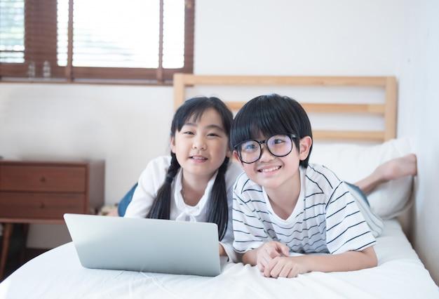 Szczęśliwa azjatykcia chłopiec i dziewczyna bawić się grę w laptopu lying on the beach na łóżku w sypialni w domu, brat i siostrzany używa notatnik robimy pracie domowej, edukaci pojęcie.
