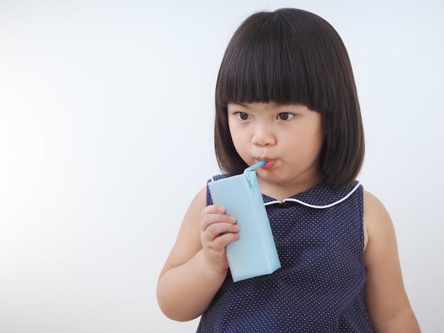 Szczęśliwa azjatykcia dzieciak dziewczyna pije mleko od kartonu pudełka z słomą.