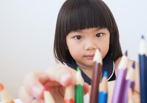 Szczęśliwa azjatykcia dzieciak dziewczyna wybiera koloru ołówek dla rysować obrazek.