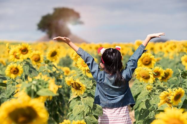Szczęśliwa azjatykcia dziecko dziewczyna ma zabawę w wiosna słoneczników polu.