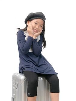 Szczęśliwa azjatykcia dziewczyna siedzi na bagażu odizolowywającym