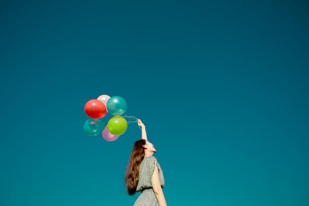 Szczęśliwa azjatykcia kobieta bawić się kolorowych balony na niebieskim niebie. koncepcja wolności