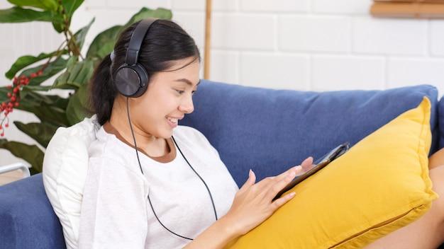 Szczęśliwa azjatykcia kobieta słucha muzyka z hełmofonami używać cyfrową pastylkę app