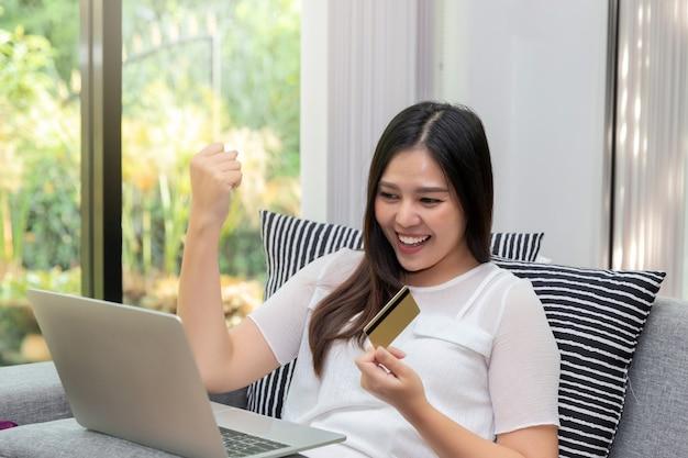Szczęśliwa azjatykcia kobieta trzyma kredytową kartę w gescie tak!