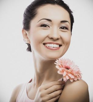Szczęśliwa azjatykcia kobieta trzyma różowego gerbera
