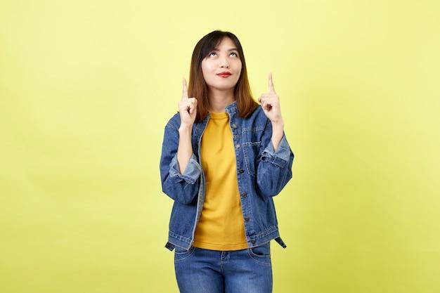 Szczęśliwa azjatykcia kobieta w dżinsowej kurtce skierowaną do góry, aby skopiować miejsce i patrząc w kamerę nad żółtą przestrzenią