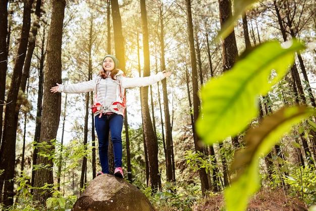 Szczęśliwa azjatykcia kobieta z plecakiem pozuje na skale