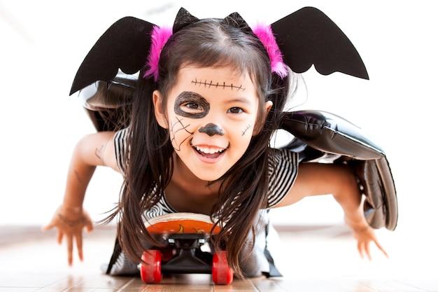 Szczęśliwa azjatykcia małe dziecko dziewczyna w kostiumach i makeup ma zabawę bawić się z rolkową deską