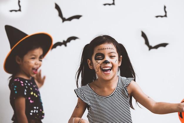 Szczęśliwa azjatykcia małe dziecko dziewczyna w kostiumach i makeup ma zabawę na halloweenowym świętowaniu