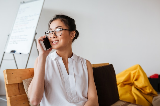 Szczęśliwa azjatykcia młoda kobieta opowiada na telefonie komórkowym