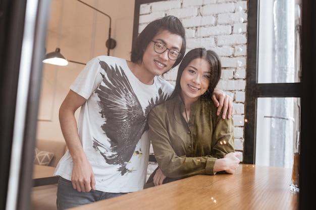 Szczęśliwa azjatykcia młoda kochająca para przy kawiarnią