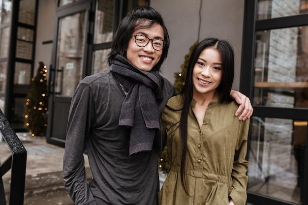 Szczęśliwa azjatykcia młoda kochająca para stoi blisko kawiarni outdoors