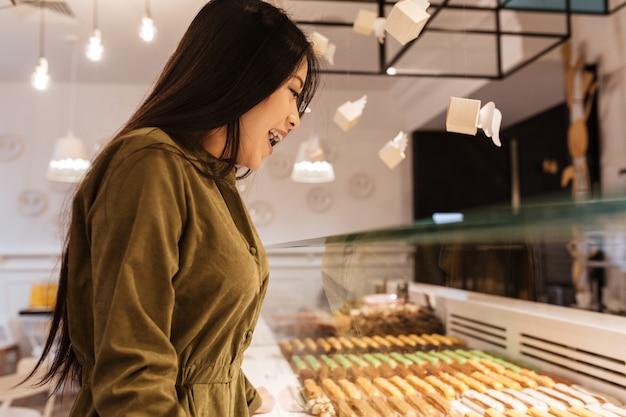 Szczęśliwa azjatykcia młodej kobiety pozycja przy kawiarnią.