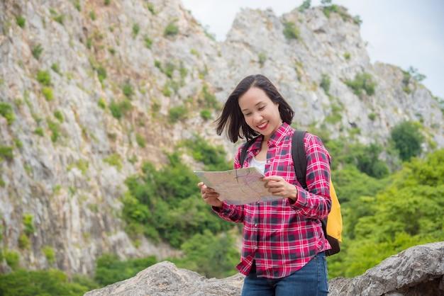 Szczęśliwa azjatykcia podróżnik kobieta z plecak pozycją przy kamiennym wzgórzem, trzymający mapę i ono uśmiecha się. letnie wakacje i wyjazd wakacyjny, przeżycie przetrwania, koncepcja stylu życia.