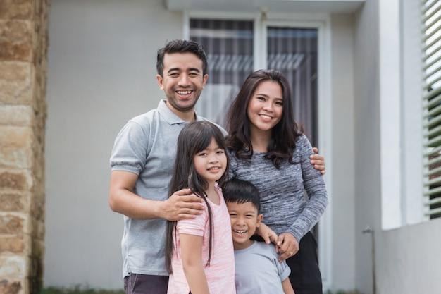 Szczęśliwa azjatykcia rodzina przed ich domem