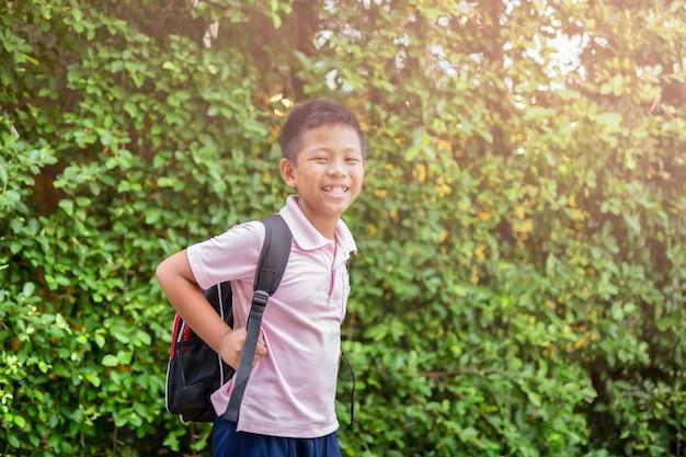 Szczęśliwa azjatykcia szkolna chłopiec w mundurze z plecakiem chodzi z powrotem do domu.