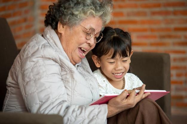 Szczęśliwa babcia azji czyta książkę wnuczka dziecka w domu, babcia uczy czytać książkę jej wnuczka.