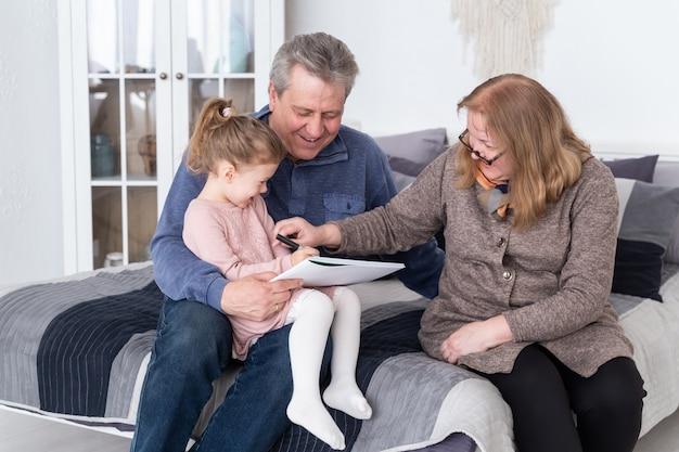 Szczęśliwa babcia, dziadek i wnuczka rysują ołówkiem, siedząc na łóżku. mała śliczna dziewczyna ze szkicownikiem siedzącym na kolanach dziadka