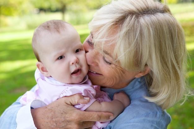 Szczęśliwa babcia trzyma ślicznego dziecka