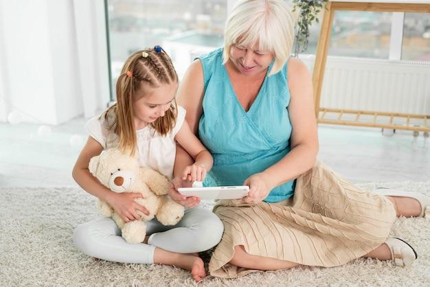 Szczęśliwa babcia z małą wnuczką za pomocą tabletu, siedząc na podłodze w pokoju dziecięcym