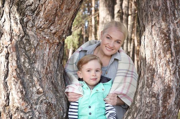 Szczęśliwa babcia z małym chłopcem w pobliżu drzewa w słoneczny dzień
