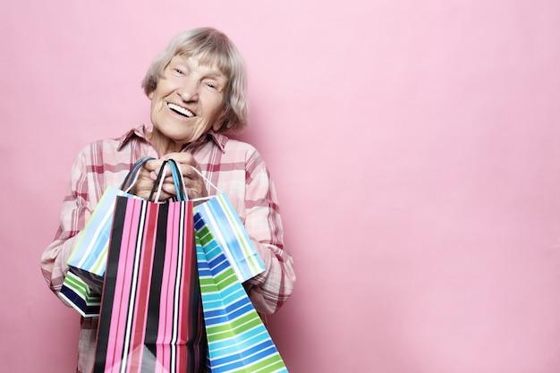 Szczęśliwa babcia z torba na zakupy nad różowym tłem. koncepcja życia i ludzi. starsza kobieta - szczęśliwy czas.