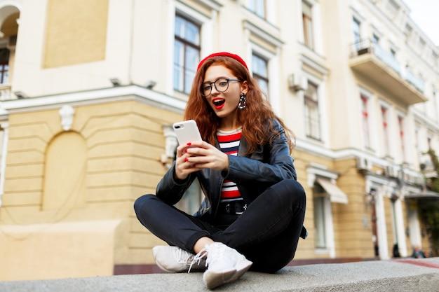 Szczęśliwa bajeczna imbirowa kobieta w stylowym czerwonym berecie na ulicy przy użyciu jej smartfona