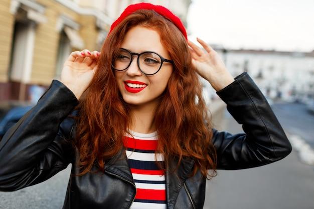 Szczęśliwa bajeczna imbirowa kobieta w stylowym czerwonym berecie na ulicy