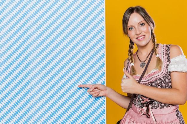 Szczęśliwa bawarska kobieta wskazuje przy wzorem
