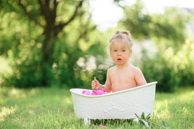 Szczęśliwa berbeć dziewczyna bierze dojną kąpiel z płatkami. mała dziewczynka w dojnym skąpaniu. bukiety różowych piwonii. kąpiel dziecka higiena i opieka nad małymi dziećmi.