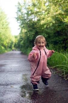 Szczęśliwa beztroska dziewczynka biegająca po kałużach po deszczu w letni dzień