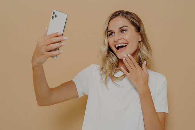 Szczęśliwa beztroska kobieta ubrana niedbale ze smartfonem robiąca selfie w studio na nagim tle, robiąca sobie zdjęcie w mediach społecznościowych, patrząca na kamerę w telefonie komórkowym z uroczym uśmiechem
