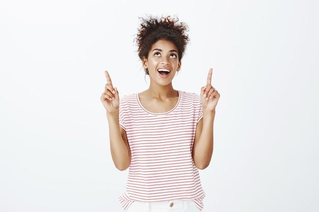 Szczęśliwa beztroska kobieta z fryzurą afro pozowanie w studio