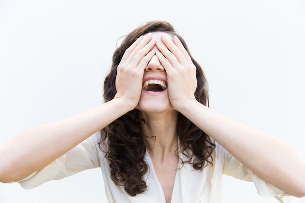 Szczęśliwa beztroska kobiety nakrycia twarz z rękami