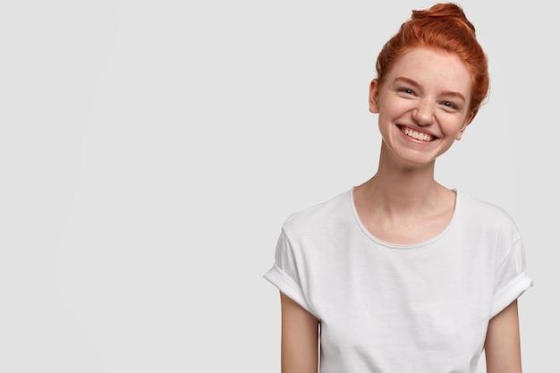 Szczęśliwa beztroska uśmiechnięta piegowata dziewczyna przechyla głowę, ma zębaty uśmiech, piegowatą skórę, ubrana w codzienne ubrania, modelki na białej ścianie z miejscem na reklamę lub tekst promocyjny