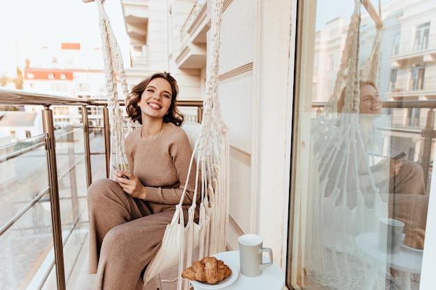 Szczęśliwa biała dziewczyna siedzi na tarasie z smacznym rogalikiem. zdjęcie śmiejącej się młodej kobiety jedzącej śniadanie na balkonie.