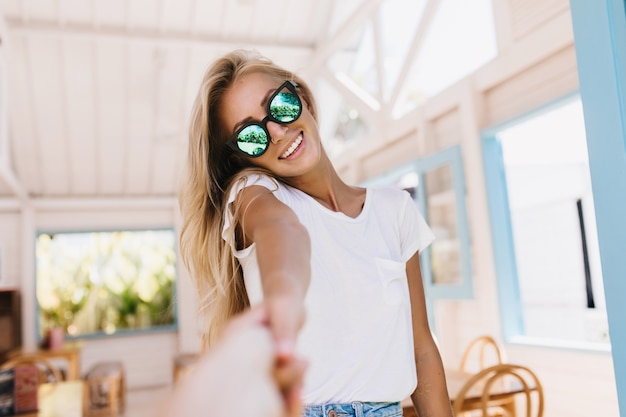 Szczęśliwa biała kobieta z opalenizną pozowanie w kawiarni. kryty portret śliczna kaukaska modelka z pięknymi blond włosami.