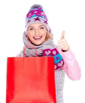 Szczęśliwa biała kobieta z torby na zakupy pokazuje kciuk do góry znak na białym tle