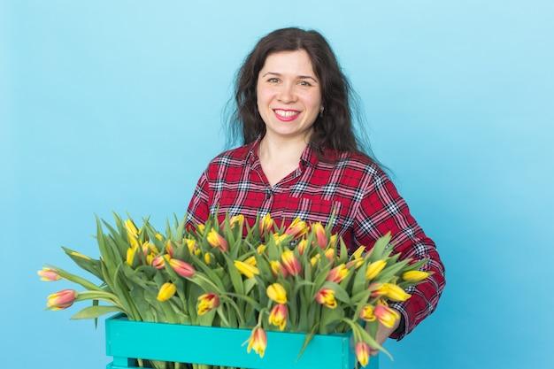 Szczęśliwa biała młoda kobieta trzyma pudełko żółtych tulipanów