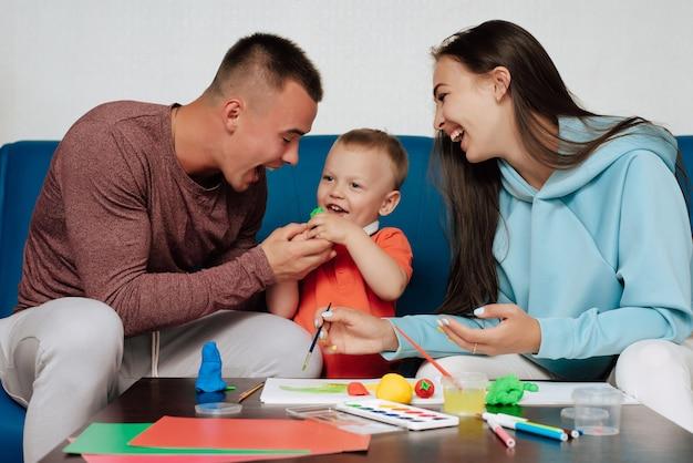 Szczęśliwa biała rodzina zajmuje się twórczą pracą i zabawą w domu. mama, tata i synek malują i rzeźbią plasteliną