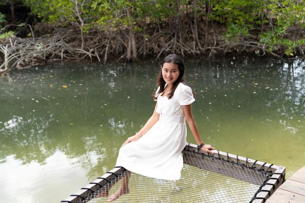 Szczęśliwa biała sukienka azjatycka kobieta siedzieć na siatce odpoczynku nad kanałem morskim w pobliżu zielonego lasu namorzynowego na wyspie phayam, ranong, tajlandia