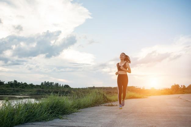 Szczęśliwa biegacz kobieta biega w parkowym jogging ćwiczeniu.