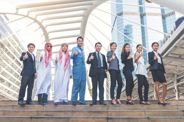 Szczęśliwa biznes drużyna robi wysokościom wręcza w miasta tle